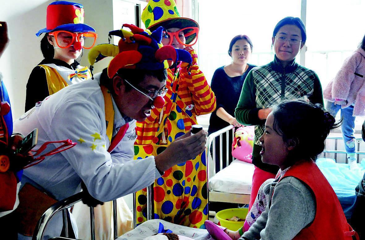 """10月31日上午,""""小丑医生""""团队来到市妇幼保健院病房,给患儿表演魔术"""