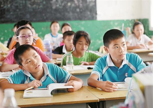 图为:红安县檀树中学七年级学生张文成(左)和张文卓兄弟俩在上课